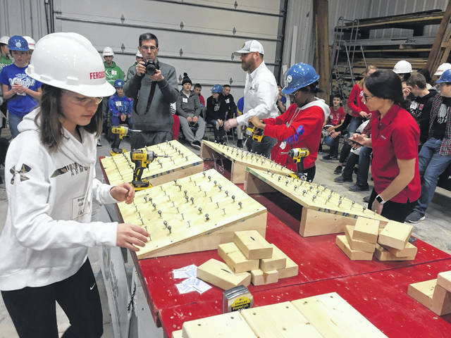 Anna eighth-grader Breanna Cobb, left, 14, daughter of Brandon and Amy Cobb, and Sidney eighth-grader Javeahna Murphy, 15, daughter of Katrina and Jimmy Murphy, moves through the course after drilling screws into pieces of wood during the Skilled Trades Ninja Challenge on Tuesday at the Upper Valley Career Center in Piqua.