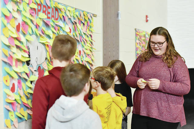 Madison Baughman, far right, 11, of Botkins, daughter of Kellie and Tom Baughman, reads a message on a heart that she took from a message board in the Botkins Local School cafeteria on Friday, Jan. 31. The hearts were put up by Botkins Leadership team members for Botkins Elementary students to pull down.