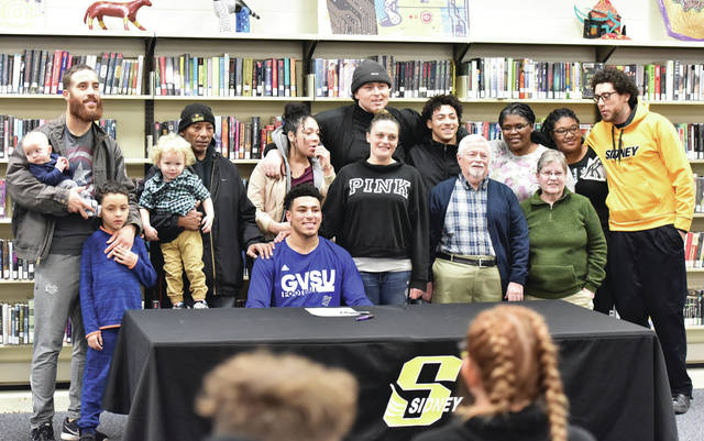Sidney senior Darren Taborn, bottom middle, poses with family members shortly after signing a national letter of intent to play football for Grand Valley State on Wednesday in Sidney High School's library.