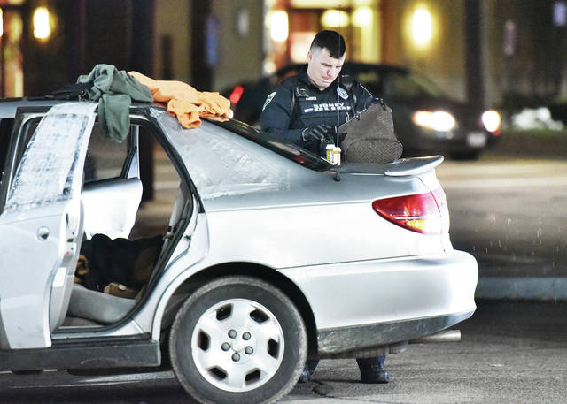A Sidney Police Officer goes through a purse in the parking lot of the Clark gas station on Court Street at around 7:45 p.m. on Monday, Feb. 17. A car was stopped and searched. Three people were arrested on a possible drug related offense.
