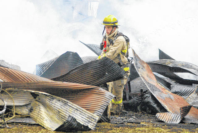 A firefighter from the Houston Fire Department clears debris Monday afternoon, Feb. 17, following a shed fire near the intersection of Fair Road and Lindsey Road. Personnel from the Lockington, Port Jefferson and Sidney Fire Departments and Houston Rescue also responded to the fire.
