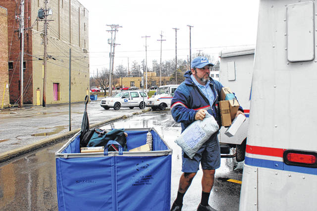 Mailman John Bernardi, of Sidney, loads his truck with packages at the Sidney Post Office Tuesday morning to deliver around the east side of Sidney. Bernardi says he always wears shorts no matter the weather, preferring to do his job comfortably.