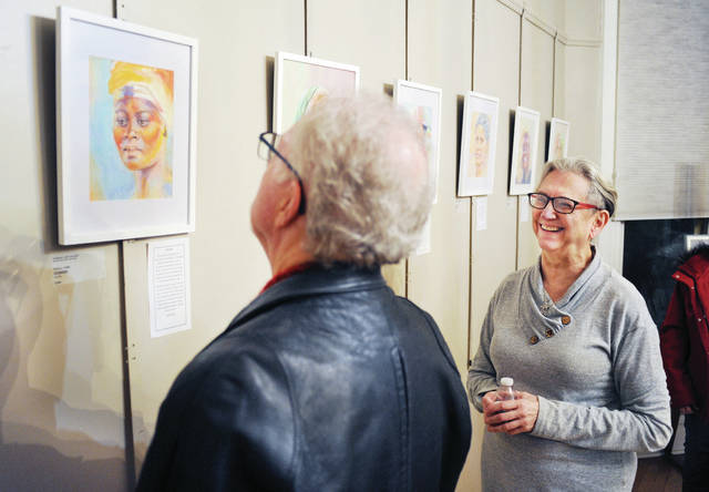 Bill Danzig, left, of Dayton, looks at one of the pastel portraits of women drawn by artist Paula Long, right, of Hilliard. The pastels are part of the Gateway Arts Council's XIX Exhibit which had its gallery opening on Friday, Jan. 31. The exhibit is a celebration of the 100th anniversary of the 19th amendment which gave women the right to vote. The exhibit of female portraits by various artists will run through Friday, March 6.