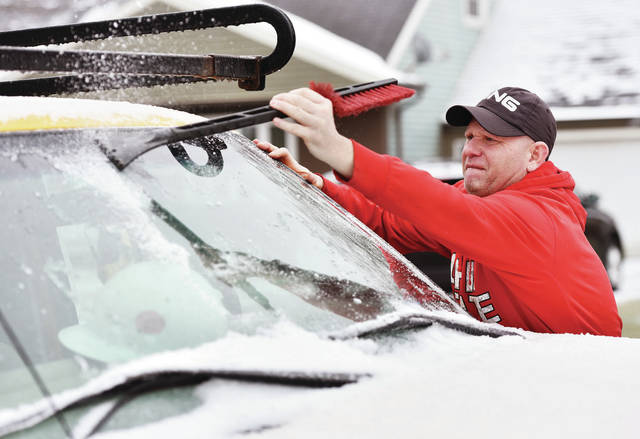 Brad Rickey, of Sidney, stretches to reach a patch of ice in the center of his work truck's windshield on Thursday, Feb. 6. Freezing rain on Wednesday evening coated the area in ice. Rickey operates heavy equipment for his job.