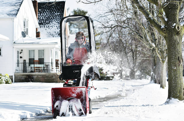 Phil Wogoman, of Sidney, clears snow from the sidewalk in front of his house on Pinehurst Street on Friday, Feb. 7. Wogoman also cleared the sidewalk in front of several of his neighbor's houses as he says he usually does when it snows.