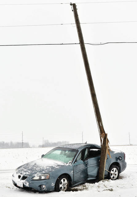 A car crashed into a utility pole snapping it along the 12600 block of Hardin-Wapakoneta Road around 4:20 p.m. on Sunday, Feb. 9. Pioneer Electric workers were waiting for another crew to help them replace the pole.
