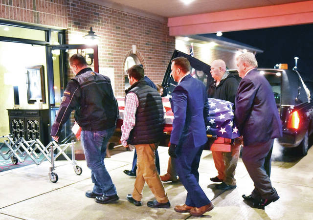 The body of Senior Airman and 2016 graduate of Sidney High School Tristen Allen Carlson is carried into Adams Funeral Home after a procession of emergency vehicles brought him down Fair Road which was lined by people holding U.S. flags. The procession was held around 9:15 p.m. on Saturday, Feb. 8, to honor the service of Carlson.