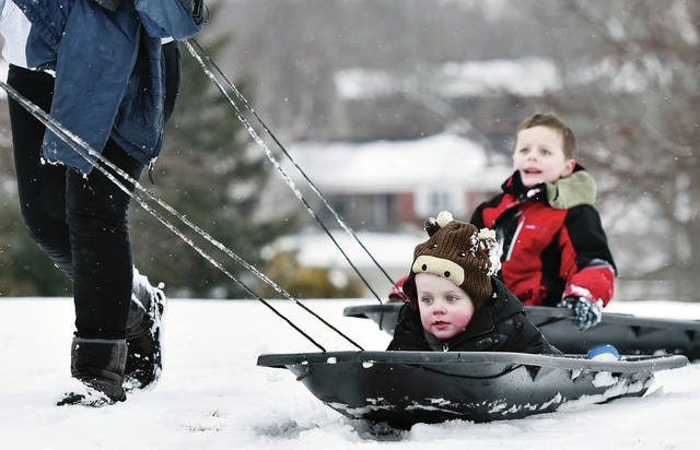 Brothers Carter Jackson, front, 3, and Lucas Jackson, 6, both of DeGraff, are pulled in sleds by their parents Josh and Jess Jackson, after two hours of sledding at the Moose Golf Course on Saturday, Feb. 8. Josh and Jess Jackson said the only other option for a good sledding hill is at Mad River Mountain but it costs more money than they want to pay.