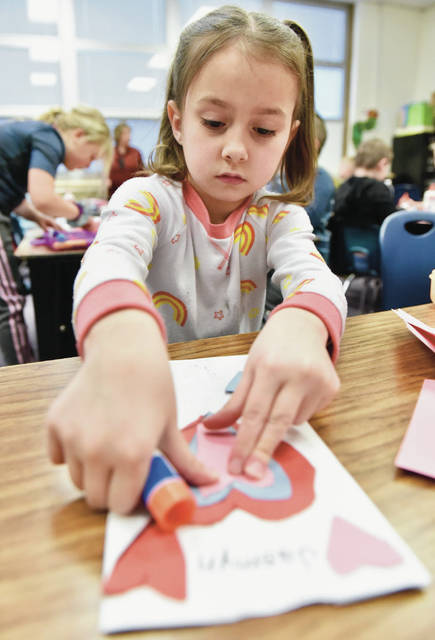 Jasmyn Russell, of Sidney, decorates a bag with paper hearts in her first grade class at Emerson Primary School on Monday, Feb 10. The first grade class of Kris Klepinger will use the bags to hold the Valentine's Day cards the students give each other on Valentine's Day. Jennifer and Jeff Martin are the guardians of Jasmyn.