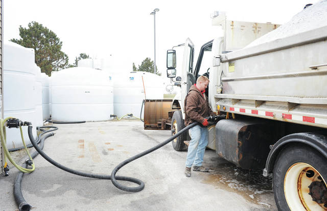 Eric Prenger, of Sidney, fills a plow with brine at the Shelby County Ohio Department of Transportation garage located at 2190 St. Marys Ave. at around 1:30 p.m. on Wednesday, Feb. 12. Brine is a mixture of salt and water that plow drivers spray to pretreat roads before snow is forecasted. Brine helps prevent ice from forming on roads. The dark lines of brine sprayed on Shelby County Roads could be seen everywhere on Wednesday afternoon. The brine was laid down in preparation for several inches of forecasted snow.