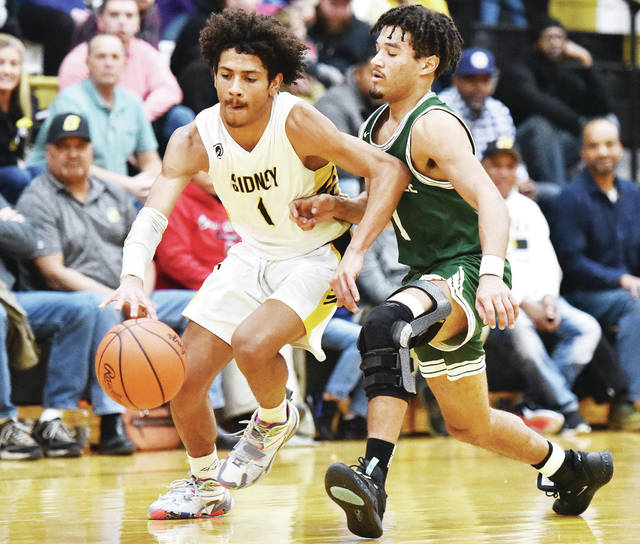 Sidney senior guard Dominick Durr makes his way past Greenville's Alex Baumgardner during a Miami Valley League game on Friday in Sidney. The Yellow Jackets secured the overall MVL title with the 56-42 win.