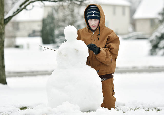 Grady Mitchell, 12, of Sidney, son of Jill and Mike Mitchell, puts the final touches on a snowman he made in his yard along Hoewisher Road on Thursday, Feb. 13.