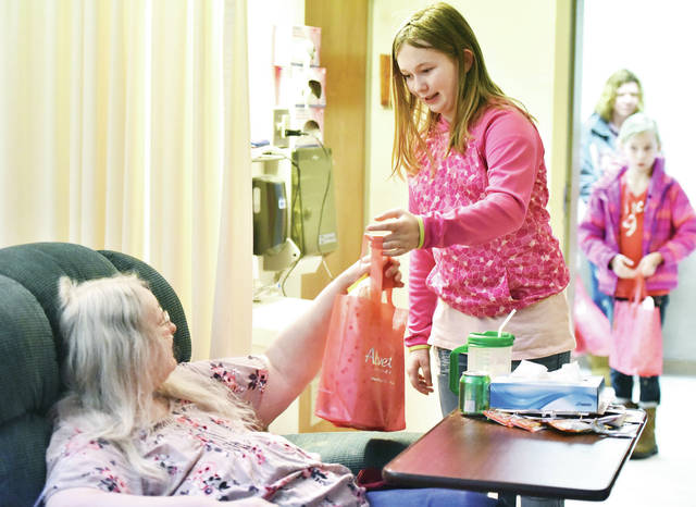 Starting Farmers 4-H Club member Lilly Tobe, right, 12, of Sidney, daughter of John and Leslie Tobe, hands a Valentine's Day bag to Fair Haven resident Karen Cales on Thursday, Feb. 13. 4-H members have been handing out the bags to local nursing homes. The bags were donated by Alvetro Orthodontics.