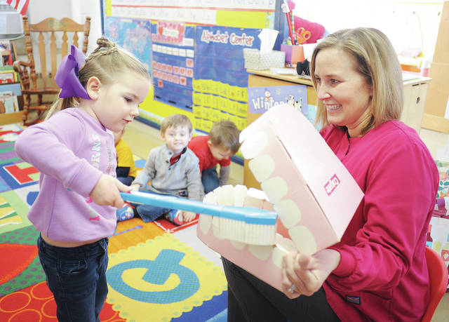 Harper Henman, left, 4, of Maplewood, daughter of Jessica and Cody Henman, learns the proper way to brush teeth from hygienist Danielle Heuker, of Anna, at the Sidney Co-op Nursery on Friday, Feb. 14.