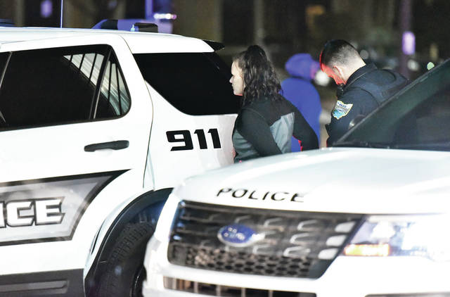 A Sidney Police Officer prepares to put a woman in a police cruiser in the parking lot of the Clark gas station on Court Street around 7:45 p.m. on Monday, Feb. 17. A car was stopped and searched. Three people were arrested on a possible drug related offense.
