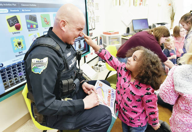 "Sidney Police Officer Bryce Stewart, left, has his nose poked by Avery Kessler, 5, of Sidney, daughter of Jason Kessler and Kalee Smith, after Stewart got done reading the book ""I'm Not Scared I'm Prepared! : Because I Know All About Alice."" Stewart came to read to the preschoolers at Kids Learning Place on Wednesday, Feb. 19. The book talks about what to do if a dangerous intruder comes to their school."
