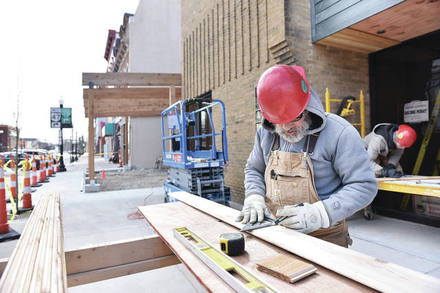 Ferguson Construction employee Doug Snow, of Indian Lake, cuts cedar shiplap siding to place above the door of what will be Tavolo Modern Italian at 101 S. Ohio Ave. on Thursday, Feb. 20. Large redwood cedar beams that can be seen behind Snow jutting out into the sidewalk will be part of a four seasons open air dining space that will have four hanging heaters and two heaters coming up from the patio, according to construction workers. The outdoor dining area opens into a bar area. The bar is adjacent to a large main dining area. In a corner of the main dining area is a smaller dining room that used to be the old bank vault. The massive vault door has been preserved.
