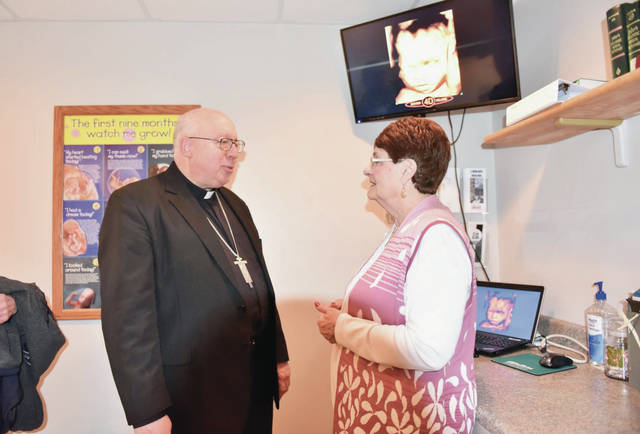 Bishop Joe Binzer, left, of Cincinnati, talks with Women's Center Executive Director Vivian Koob, of Dayton, in front of a readout from the new 3D/4D ultrasound machine provided by the local Knights of Columbus councils. According to Development Officer Ashley Schroeder Binzer came to bless the newly expanded Women's Center which now has 4 new consultation rooms, a classroom, and a maternity clothes room. Security measures have also been expanded. An open house was held on Sunday, Feb. 26.