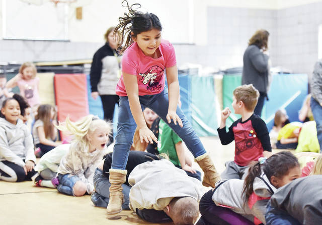 Aaliyah Bishop-Johnson, 8, of Sidney, daughter of Leanna Wallace, plays a game of Leapfrog with her first grade classmates during recess at Longfellow Primary School on Friday, Feb. 28. Saturday, Feb. 29 is Leap Day.