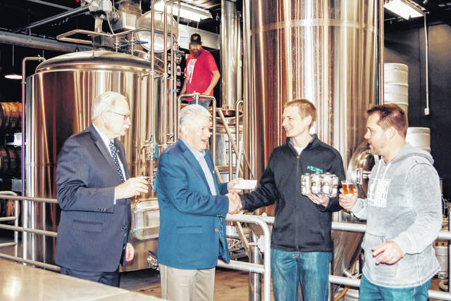 Nick Wolters, of Sidney, receives prize money and the first six-pack of Sidney 1820 Export from Shelby County Commissioner and Sidney Bicentennial Beer Subcommittee Chair Tony Bornhorst as Moeller Brew Barn owner Nick Moeller, far right, and Sidney Mayor and Bicentennial Committee Chair Mike Barhorst sample the first glasses of the beer, especially brewed for Sidney's Bicentennail.