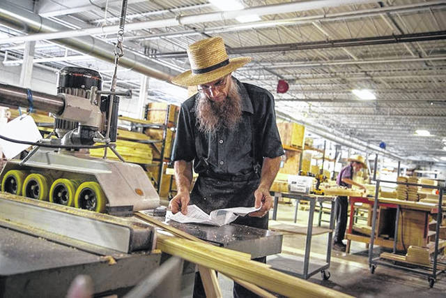 An amish man looks over a manual while working in a factory.