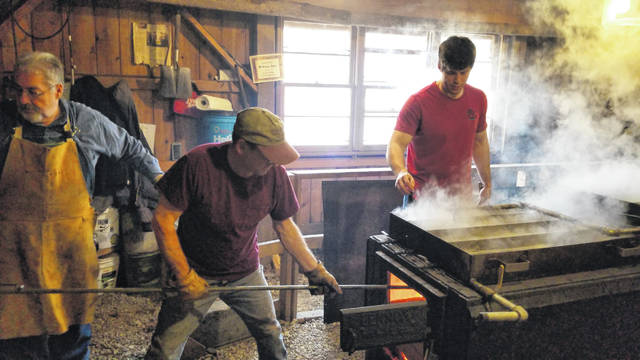 Volunteers Rick Normile and Neil Schmidt work with staff Michael Colamarino by boiling sap in the sugar shack.