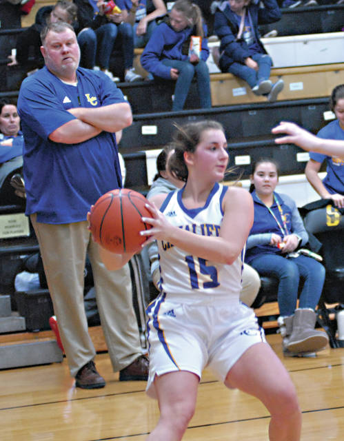 Lehman Catholic's Hope Anthony passes the ball as Lehman coach Craig Hall looks on during a Division IV sectional opener on Saturday in Sidney.