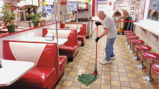 Jerry Hoaglin, of Sidney, mops the floor at The Spot Restaurant shortly after it closed Sunday night. It was the final day the restaurant and all others in Ohio were allowed to have dine-in service. Gov. Mike DeWine declared earlier in the day that all dine-in service is suspended until further notice. Hoaglin said he has worked at the restaurant for more than 20 years and is concerned about how business will be affected in coming weeks. The Spot and many other area restaurants will continue to offer carryout and delivery service.
