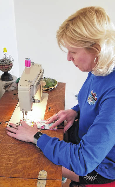 Christine McKenzie, executive administrative assistant to the president of Airstream, sews one of the personal protective equipment which will be used by heath care workers.