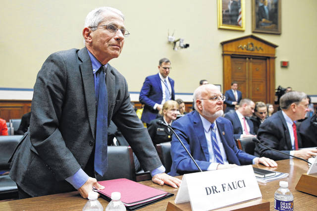 Dr. Anthony Fauci, left, director of the National Institute of Allergy and Infectious Diseases, departs during a recess after testifying before a House Oversight Committee hearing on preparedness for and response to the coronavirus outbreak on Capitol Hill in Washington on Wednesday.   Patrick Semansky | Associated Press