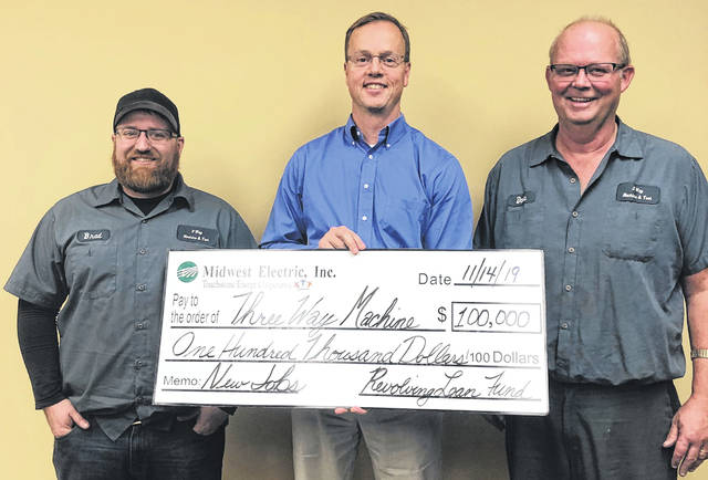 Midwest Electric CEO Matt Berry, center, presents a $100,000 loan to 3 Way Machine and Tool Supply owners Brad Feltz, left, and Dave Moorman, right, to assist with the purchase of an expansion building in Marion Township Industrial Park.