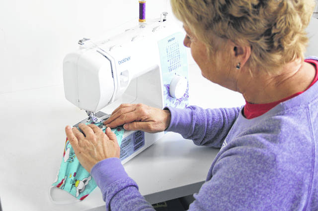 Connie Monnin sews a mask in her home while practicing social distancing. Monnin took on the project when she heard that there was a shortage of masks and a need for them in hospitals and long-term care facilities.