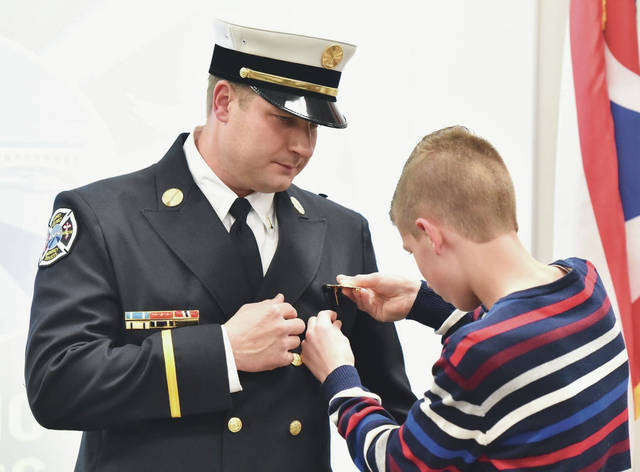 Alex Lundy, 6, pins a badge onto his dad's uniform Monday afternoon, March 2, after Lt. Sidney Firefighter Brian Lundy was sworn-in as the department's newest lieutenant. The ceremony was held in the Nancy Adams Training Center at Sidney Fire Department's Station 1.