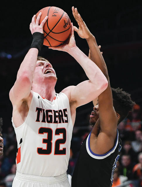 Jackson Center junior forward Aidan Reichert shoots with pressure from Cincinnati Christian's Devin McKinnon during a Division IV regional semifinal on Tuesday at UD Arena. Reichert led the squad with 18 points and had eight rebounds.