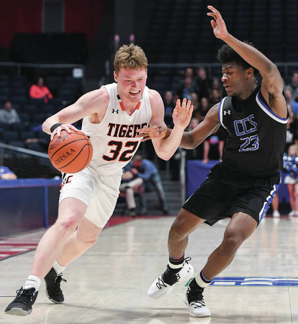Jackson Center junior forward Aidan Reichert dribbles with pressure from Cincinnati Christian's Cameron Rogers during a Division IV boys basketball regional semifinal on March 17 at UD Arena. Reichert has named first team all-Ohio in Division IV.