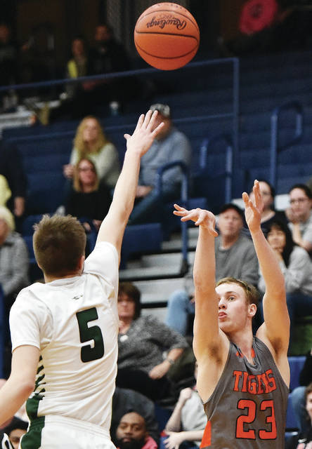 Jackson Center's Garrett Prenger shoots over Troy Christian's Isaac Gray during a Division IV district semifinal on Saturday at Garbry Gymnasium in Piqua.