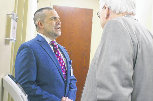 Dr. Michael Beyer from Wilson Health talks with Sidney Mayor Mike Barhorst on Wednesday in the new Wilson Health Clinic at the school's Board of Education Office.