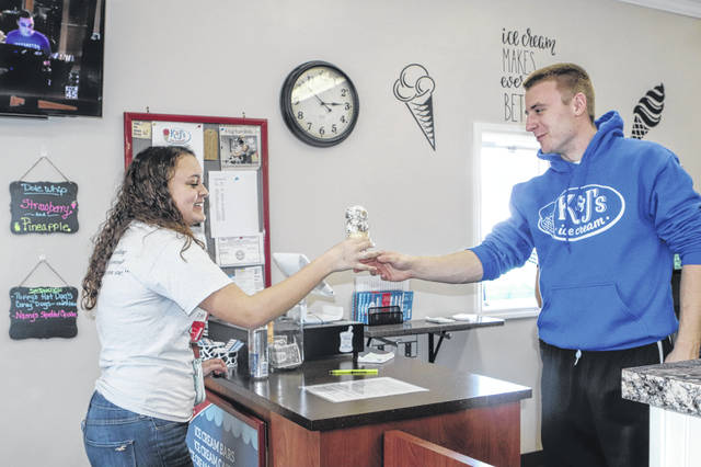 Delaney Mullen, 15, daughter of Kara Mullen, of Jackson Center, gets her ice cream from James Curlis, one of the owners of K&Js Ice Cream Sunday afternoon. Kim Curlis is also an owner the the store. K&J's opened for the season Saturday. their hours are Monday to Saturday, noon to 9 p.m., and Sunday 1 to 9 p.m.