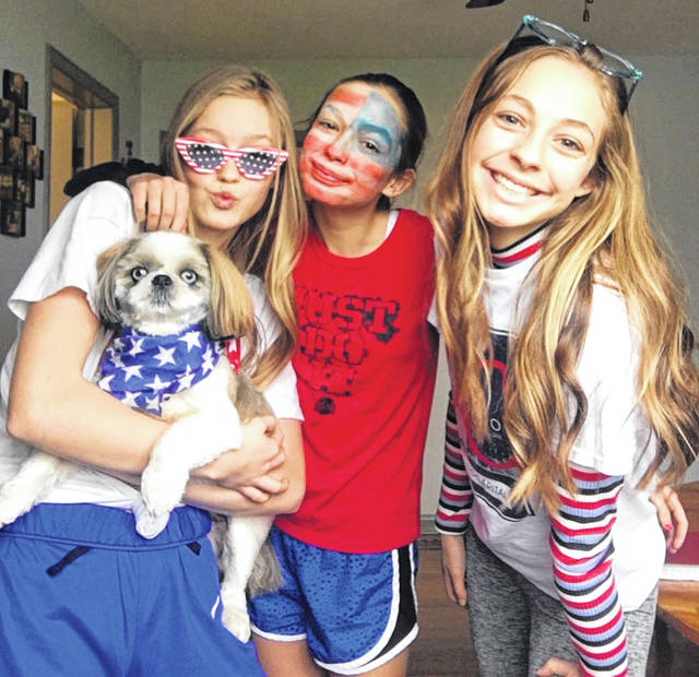 Botkins Local School's remote spirit week began with America Monday, which encouraged students to wear red, white and blue. Pictured, left to right, are eighth grader Malanie Maurer, fifth grader Maguire Maurer and high school junior Makenna Maurer. Also pictured is the girls' dog, Maverick.