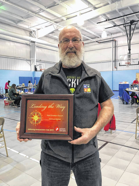Neal Mutter holds a plaque after making his 300th lifetime blood donation at First Christian Church in Springfield. Mutter makes it a point to donate blood every 8 weeks and says it's part of his routine.