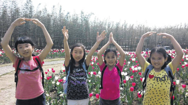 Some of Sarah Bellmer's students at Transformation Academy in Shanghai make the O-H-I-O sign that is popular with Ohio State fans with their arms. The students were some of Bellmer's original fifth grade students and now are in the 10th grade.