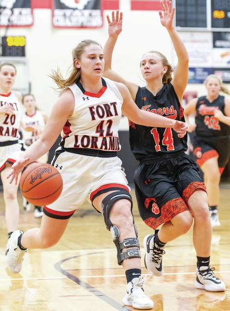 Fort Loramie senior forward Marissa Meiring dribbles by Jackson Center's Ashley Mullenhour during the second half of a Shelby County Athletic League game on Jan. 30 in Fort Loramie. Meiring tore the ACL in her left knee as a freshman but has played the last three years and, along with three other seniors, is providing critical leadership as the unbeaten Redskins head into a regional semifinal versus Danville on Thursday night at Vandalia-Butler. Wilson Health Sports Medicine, which provided the care leading to Meiring's full recovery, is featured in ScoresBroadcast's coverage of local high school sports. Next week, SCORES webcasts game No. 1500 since its start in 2006 and 2007.