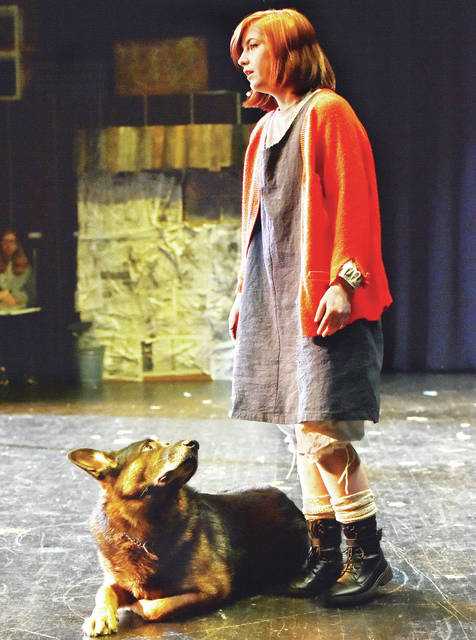 Annie, played by Kiele Suttles, 15, of Sidney, daughter of Tim and Leanne Suttles, sings after discovering a homeless dog, played by canine officer Hiro, during a practice run of Annie at Jackson Center Local Schools on Wednesday, March 4.