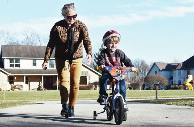 Kathy Cavinder, left, follows her grandson, Jaxx Sarver, 3, both of Sidney, as he bikes up her driveway on Wells Drive. Jaxx was taking advantage of warm temperatures on Wednesday, March 5, to ride the bike he was given as a birthday present in August. Jaxx had no problem going down the driveway but coming back up required a little help from Cavinder. Jaxx is the son of Emilie Cavinder and Austin Sarver.