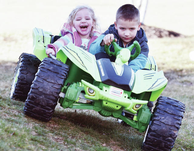 Piper Gockley, left, 2, laughs as her brother, Connor Landrum, 5, both of Sidney, navigates a steep hill in their Twinbrook Plaza backyard from behind the wheel of a Power Wheels Dune Extreme on Thursday, March 5. They are the children of Tracey Landrum and Chris Gockley.