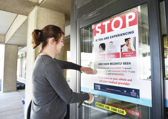 Wilson Health Volunteer Coordinator Jenny Meyer, of McCartyville, tapes a COVID-19 warning sign to the main entrance to Wilson Health on Friday, March 13. The sign warns people who think they have COVID-19 not to enter the hospital but to return to their vehicle and call their medical provider.