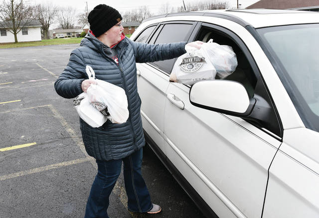 Teachers Aid Sara Cowan, of Sidney, hands out a school lunch in the Longfellow Primary School parking lot on Tuesday, March 24. Lunches are still being handed out despite school buildings being closed.