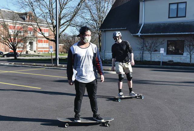 Jamari Batusin, left, and Louis Hauff Jr., both of Sidney, wear face masks to protect against COVID-19 as they skateboard in the parking lot of the First United Methodist Church on Wednesday, March 25. After skateboarding downtown for a while the two said they were heading for Tawawa Park.