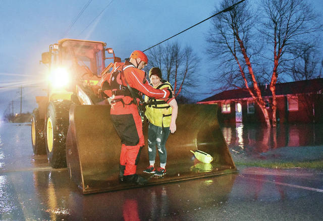 Sidney firefighter Bryan Ramge, left, helps Shelly Swiger, down from a front loader that rescued Swiger from her car that was inundated with flood waters on West Russell Road at its intersection with North Kuther Road on Saturday, March 28. Swiger said she saw the flooded intersection as she was approaching it. She started to turn around and go back the way she came when a surge of water stalled her car and surrounded it. The water started coming into the car. Swiger estimated the water rose Eight inches in one minute. After her car stalled Swiger rolled down her window which she crawled out of when the front loader arrived to pick her up with the help of Ramge and drive her through the flooded intersection.