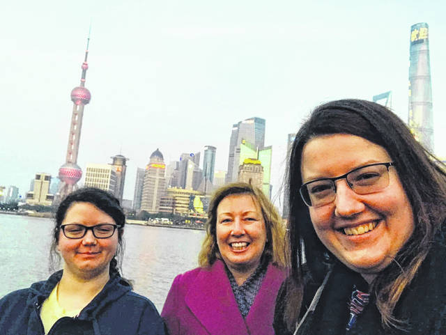 Sarah Bellmer, right, stands in front of the Shanghai skyline with her sister, Amy Bellmer, left, and Amy Bellmer's coworker, Phyllis Berg.